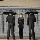 two businessmen facing away holding umbrellas and businesswoman front view