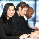 Portrait of a young businesswoman and two businessmen sitting at a meeting (blurred)