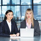 Portrait of two young businesswomen sitting with a laptop