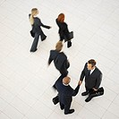 Elevated view of business executives walking in an office and two business executives shaking hands
