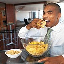 close up of businessman sitting eating crisps from a bowl and a bowl of peanuts