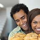 close up a couple looking at freshly made cookies and smiling