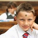 Close-up of a boy (9-11) in a classroom with a star on his forehead and girl in the background
