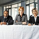 portrait of a panel of three interviewers looking serious