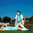 female soccer player (16-18) lying on ground injured with teammate (16-18) holding her knee