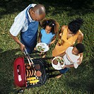 elevated view of two generation family at barbeque with the father serving and children holding plates