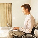 side view of a man sitting in a wheelchair working on a laptop