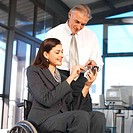 businesswoman sitting in a wheelchair showing a businessman something on a pda