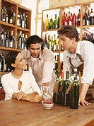 mid adult man selling wine to a young couple