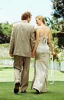 rear view of a newlywed couple walking together holding hands on a lawn