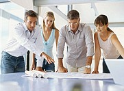 group of business executives looking at a blueprint in an office