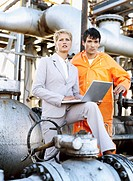 female engineer standing with a mechanic and using a laptop