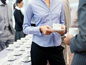 mid section view of two business executives holding cups of coffee at a seminar