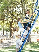 side profile of two boys and a girl climbing on a ladder