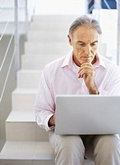 mature man sitting on stair and using a laptop