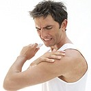 portrait of a young man touching his shoulder in pain