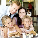 portrait of parents standing at breakfast with their son and daughter