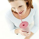 high angle view of a woman drinking a fruit smoothie