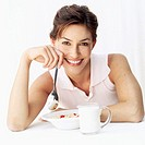 Portrait of a woman holding a spoon over a plate of breakfast cereal with a cup of milk
