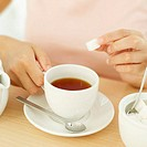 Close-up of a woman´s hand holding a sugar cube over a cup of tea