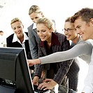 a group of young business executives viewing a computer screen together