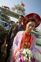 Couple going to their wedding, crossing ariver by ferry. Vihn Long, Mekong Delta. Vietnam