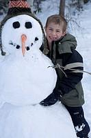 Boy (6-7) posing with snowman, portrait