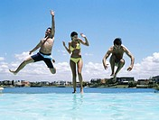 Young woman screaming as two young men jump into infinity pool