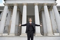 Portrait of a businessman standing outside a building with pillars
