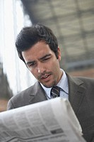 Low angle view of a businessman reading a newspaper