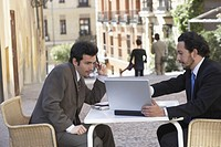 Side profile of two businessmen looking at a laptop