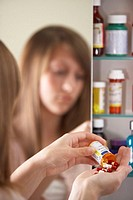 Teenage girl (13-15) pouring out pills into hand, rear view