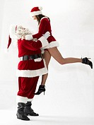 Santa Claus lifting young woman in santa outfit, side view