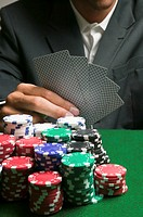 Large stack of poker chips in front of man playing cards, close-up