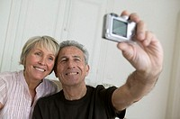 Senior couple taking photograph of themselves in room, smiling