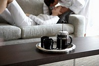 Man kissing woman on sofa (focus on French press in foreground)