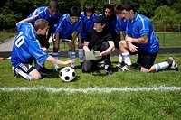Coach instructing teenage male (16-20) soccer players