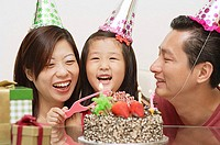 Girl with birthday cake, parents on either side smiling