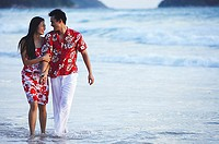Couple walking on beach, ankle deep in water, holding hands