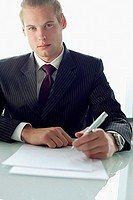 Businessman sitting at table with pen and paper, looking at camera