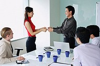Executives exchanging business cards in meeting room