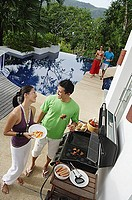 Couple grilling food over barbeque