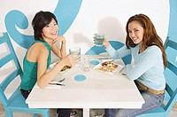 Young women having lunch in cafe, raising water glasses to camera
