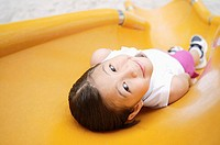 Girl lying on slide, smiling at camera