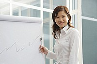 Businesswoman looking at camera, standing next to flipchart