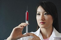 Female doctor looking at syringe, serious expression