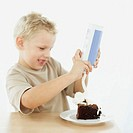 side view of a boy spraying whipped cream on a slice of chocolate cake