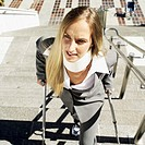 Elevated view of a businesswoman walking up a flight of stairs outdoors with crutches