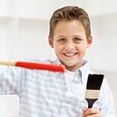 portrait of a boy holding a stick of dripping red paint