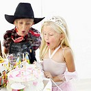 Close-up of a boy and girl blowing out birthday candles